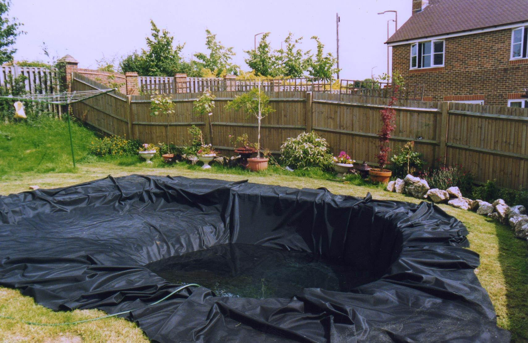 На мешковину аккуратно раскладывают пленку, плотно прижимая ее ко всем изгибам и постепенно наполняя пруд водой