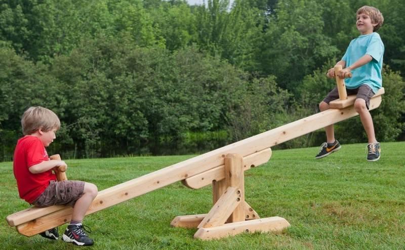 Длинная доска с подставкой посередине (балансир). Рассчитана на 2 человек, сидящих по обоим концам доски и поочередно отталкивающихся от земли ногами
