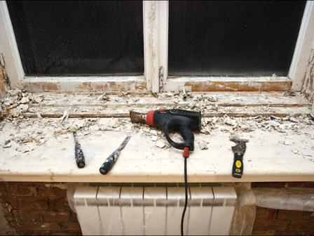 Используя монтажный фен, очищаем деревянные окна от краски